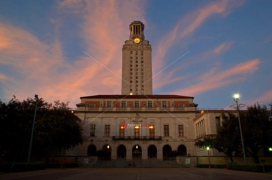New photo of pink sunset on the university campus clock tower during dusk evening in Austin, Texas, USA.
