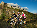 Mountain bikers Matt Hadley (left), Tricia Wilson (right) and Stefan Grecu (center) are biking together at the Canmore Nordic Center in Canmore, Alberta, Canada.