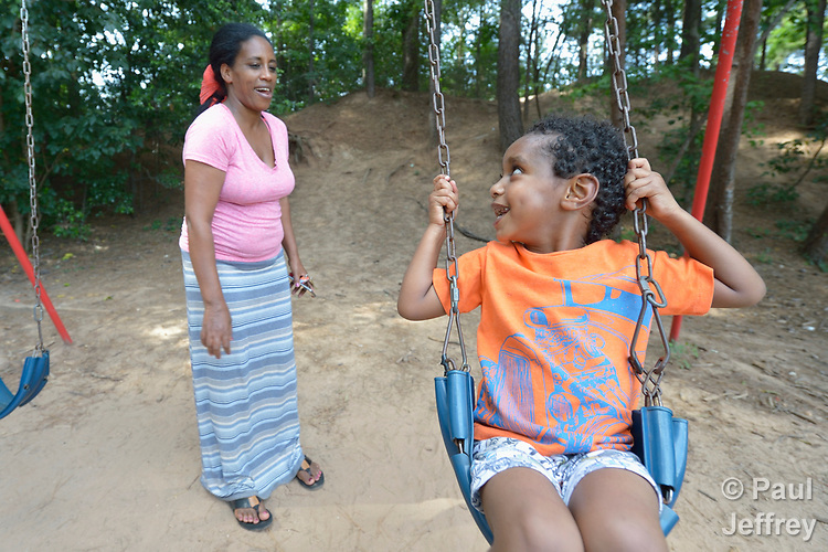 Three-year old Youel swings with help from his mother, Tirhas Drar Brehane, in a playground in Durham, North Carolina. <br /> <br /> Refugees from Eritrea, the boy and his mother were resettled in Durham by Church World Service, which resettles refugees in North Carolina and throughout the United States.<br /> <br /> <br /> Photo by Paul Jeffrey for Church World Service.