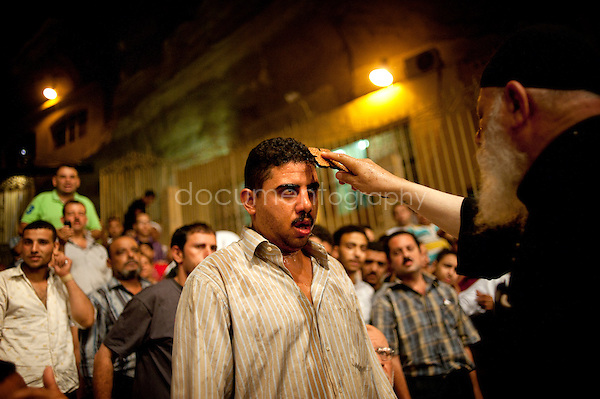 A man among the crowd of the devoted of St. Simeon Church receives an exorcism. <br />