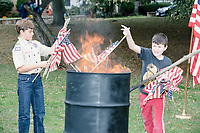 Boy Scouts and Cub Scouts dispose of old US flags by burning them in a flag retirement ceremony in Belmont, Massachusetts, USA, on Sat. Oct. 14, 2017. Flag retirement ceremonies are intended to give a dignified end to flags no longer fit to serve as a symbol for the United States of America. The ceremony was organized by Eagle Scout candidate Robert Mountain, 17, of Belmont Boy Scout Troop 66 as his Eagle Scout project.  The ceremony was held in park area surrounding Clay Pit Pond near Belmont High School.