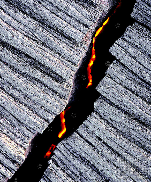 Crack in pahoehoe lava with active flow of lava beneath from Kilauea Volcano, Hawaii Volcanoes National Park, Big Island