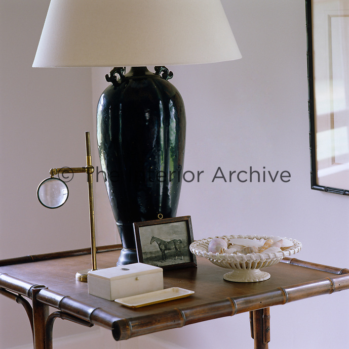 A detail of a side table in the living room with a black Chinese lamp, a dish of shells and a magnifying glass