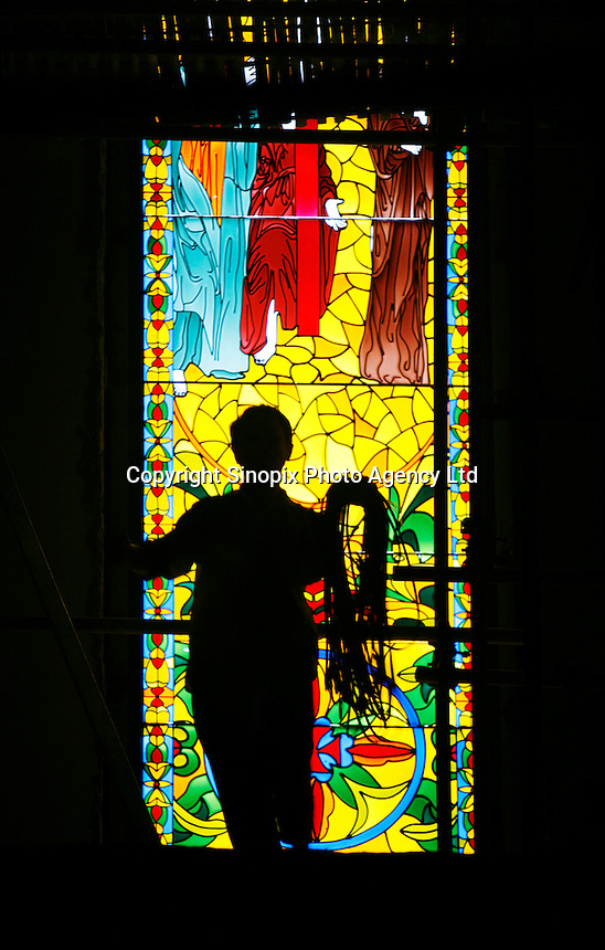 "A worker carrying ropes passes in front of a stained-glass window at a mock chapel being built in Thames Town, in Shanghai, China. Thames Town is one of several satellite townships that Shanghai is building in hopes of luring residents away from the city centre, and claims to allow people to ""taste authentic British style of small town""..21 Jul 2006"