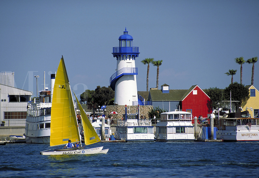 Scenic shot of Fisherman's Landing with sailboat in foreground. Lighthouse, tourist attraction, shops, sailing, recreation. Marina del Ray CA USA Fisherman's Landing.
