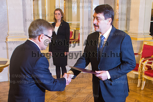 Hungary's newly minted central bank Governor Gyorgy Matolcsy (L) shake hands with Janos Ader (R) president of Hungary during the swearing-in ceremony at the Presidential palace in Budapest, Hungary on March 06, 2013. ATTILA VOLGYI