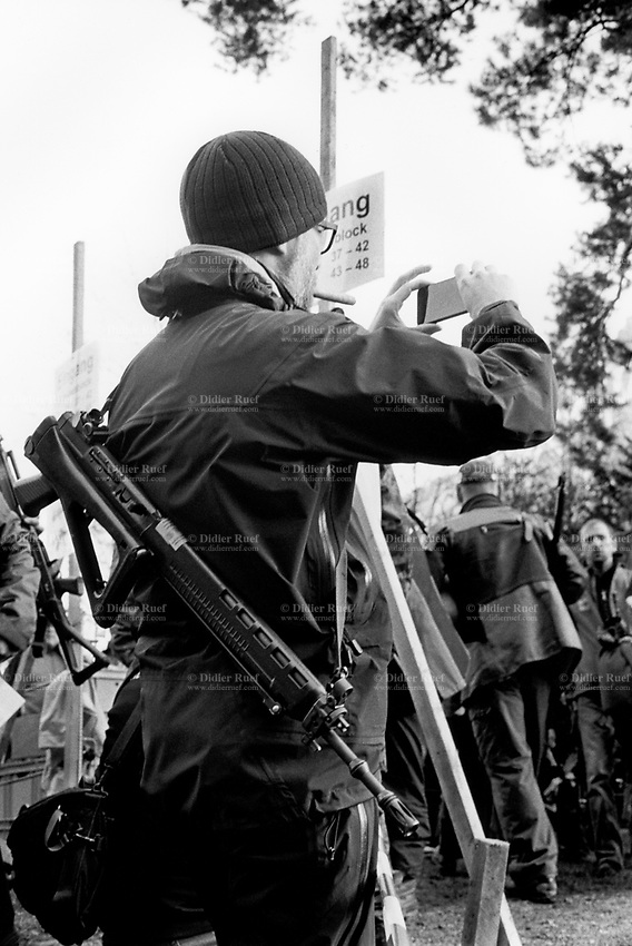 """Switzerland. Canton Uri. Rütli. A competitor and member of the riflemen's association holds on his back his automatic or semi-automatic assault rifle SG 550 during the Rütlischiessen. He takes a picture with an iPhone and smokes a cigar. Rütli or Grütli is a mountain meadow overlooking the lake Lucerne where the oath of the Rütlischwur for the forming of the Old Swiss Confederacy is said to have occurred as the legendary turning-point in the pursuit of independence. To commemorate this historic event, the riflemen's association of Lucerne organized the Rütli rifle match (Rütlischiessen) in 1862. It is held every year on the Wednesday before Martinmas (Saint Martin's Day). Thousand competitors from all over Switzerland fire their fifteen shots at targets arranged on a cliff. The SG 550 is an assault rifle manufactured by Swiss Arms AG (formerly Schweizerische Industrie Gesellschaft) of Neuhausen, Switzerland. """"SG"""" is an abbreviation for Sturmgewehr, or """"assault rifle"""". The rifle is based on the earlier 5.56mm SG 540 and is also known as the Fass 90 or Stgw 90. An assault rifle is a selective-fire rifle that uses an intermediate cartridge and a detachable magazine. iPhone is a line of smartphones designed and marketed by Apple Inc. They run Apple's iOS mobile operating system. 9.11.2016 © 2016 Didier Ruef"""
