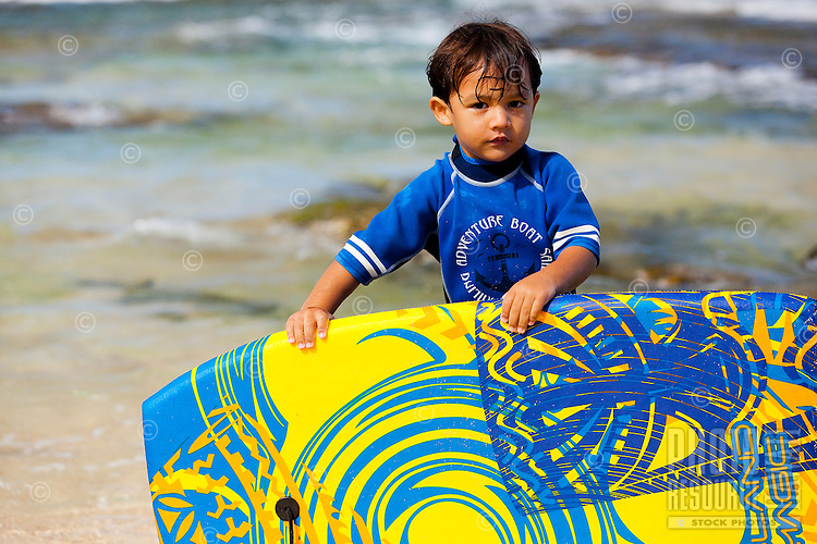 A young local Hawaiian boy holds a bodyboard on a beach on O'ahu.
