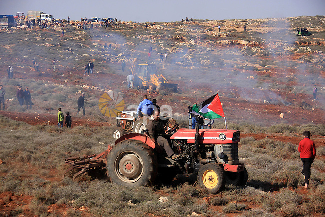 Israeli soldiers fire tear gas canisters at Palestinian farmers as they plant trees during a protest against the uprooting of trees belonging to palestinians over farming land between the Jewish settlement Shiloh and the West Bank the village of Qusrah near Nablus .Sunday, Jan. 23, 2011. Photo by Wagdi Eshtayah