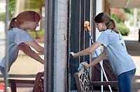 NWA Democrat-Gazette/DAVID GOTTSCHALK Jenna Symanitz, with Owens Janitorial, uses a hand squeegee Monday, July 8, 2019, to finish a bottom window on a downtown building on Emma Avenue in Springdale. Symanitz was able to finish the front in the shade before it was exposed to direct sun.