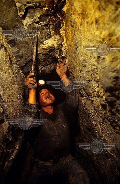 A miner works underground in the tin mines of Siglo XX.