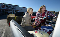 NWA Democrat-Gazette/ANDY SHUPE<br /> Tonya Bryant (right) of Prairie Grove and her daughter, Shai Bryant, write messages about Nebraska with shoe polish Thursday, March 21, 2019, on their pickup while seeking donations of livestock supplies and feed at Tractor Supply in Farmington before heading out to Elkhorn, Neb., to assist in flooding recovery. Bryant plans to return to collect more feed and veterinarian supplies from 8 to 10 a.m. Saturday at Tractor Supply in Farmington before driving back to Nebraska. Bryant is working with No Town Left Behind and Guiding Spirit Animal Rescue Organization in her efforts and plans to make as many trips as necessary until people stop making donations.