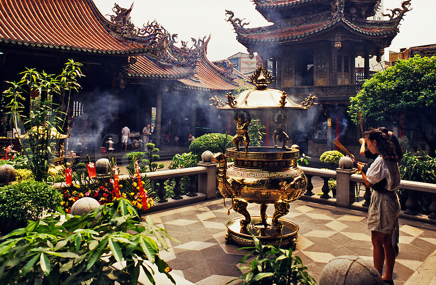Taiwan. Taipei. Lung Shang Temple.  Buddhist. Young girls offering incense..