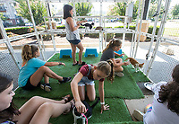 NWA Democrat-Gazette/BEN GOFF @NWABENGOFF<br /> Guests play with cats in the 'catio' outdoor area Saturday, Oct. 5, 2019, at Purr Catfe in Fayetteville. The non-profit is open for 'Purr Therapy' visits and all the cats are available for adoption.