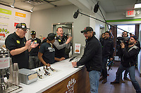 "Morgan Spurlock applauds the first customer at the opening of  ""Holy Chicken,"" a faux fast food restaurant in Columbus, Ohio, where a documentary crew recorded his interaction with customers who thought they were dining at a new type of fast food restaurant. However, the entire location was designed to be part of his documentary highlighting the marketing of food that may not be as healthy as it is stated in advertisement, banners, and notices at the restaurant."