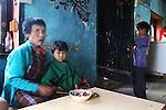 Watching television. A roadside restaurant, cafe, shop in rural Punakha, Bhutan..Bhutan the country that prides itself on the development of 'Gross National Happiness' rather than GNP. This attitude pervades education, government, proclamations by royalty and politicians alike, and in the daily life of Bhutanese people. Strong adherence and respect for a royal family and Buddhism, mean the people generally follow what they are told and taught. There are of course contradictions between the modern and tradional world more often seen in urban rather than rural contexts. Phallic images of huge penises adorn the traditional homes, surrounded by animal spirits; Gross National Penis. Slow development, and fending off the modern world, television only introduced ten years ago, the lack of intrusive tourism, as tourists need to pay a daily minimum entry of $250, ecotourism for the rich, leaves a relatively unworldly populace, but with very high literacy, good health service and payments to peasants to not kill wild animals, or misuse forest, enables sustainable development and protects the country's natural heritage. Whilst various hydro-electric schemes, cash crops including apples, pull in import revenue, and Bhutan is helped with aid from the international community. Its population is only a meagre 700,000. Indian and Nepalese workers carry out the menial road and construction work.
