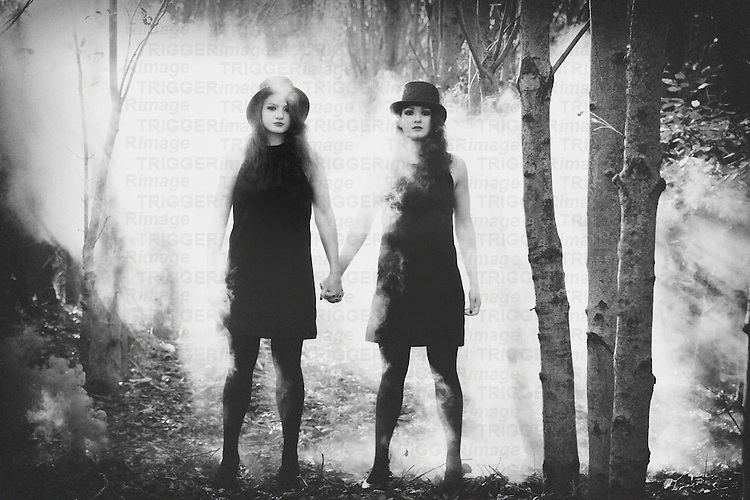 Twins are holding hands in the forest around them fog