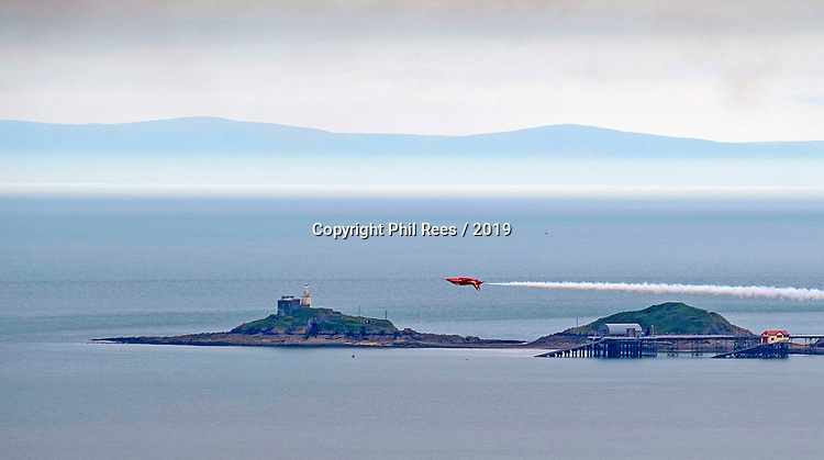 The RAF Red Arrows performing at the Wales Airshow over the Mumbles headland and Lifeboat Station in Swansea Bay this afternoon.