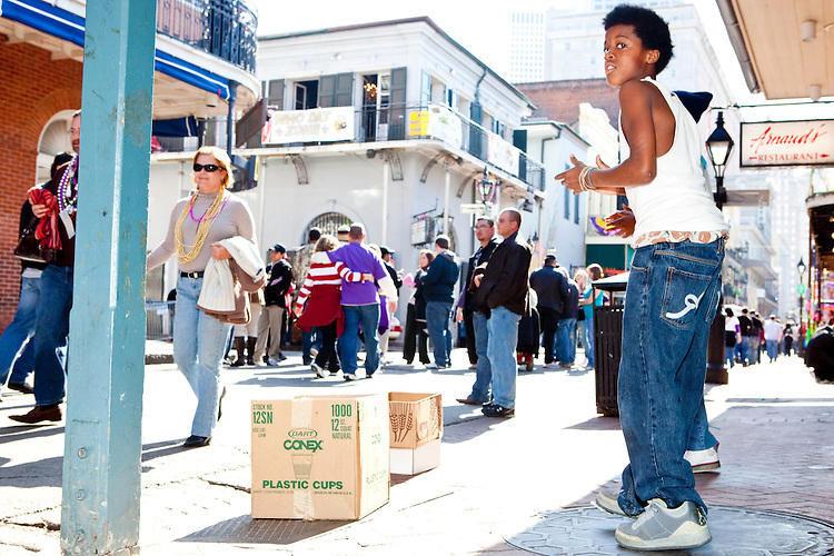 Local children use crushed up aluminum cans on their feet to dance for tips on Bourbon Street during Mardi Gras in New Orleans on February 14, 2010.