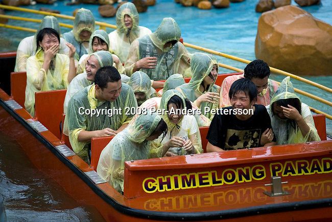 GUANGZHOU, CHINA OCTOBER 4: Chinese tourists ride a flume ride water attraction at Chimelong Paradise Theme Park on October 4, 2008 outside Guangzhou, China. Millions of Chinese took a weeklong break during the National Holiday and one of the Golden weeks during the year. Chimelong is one of the best and most popular amusement parks in China with attractions such as a driving safari, animal shows and the biggest rollercoaster in the world with 10 loops. Chinese people love theme parks and new ones are opening constantly. It's estimated that there's about 2400 theme parks in the country. (Photo by Per-Anders Pettersson)..