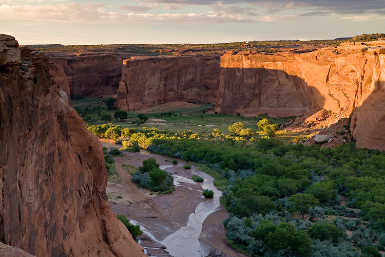 Viewed from Tsegi Overlook, the setting sun illuminates the De Chelly sandstone walls after a summer monsoon storm passes