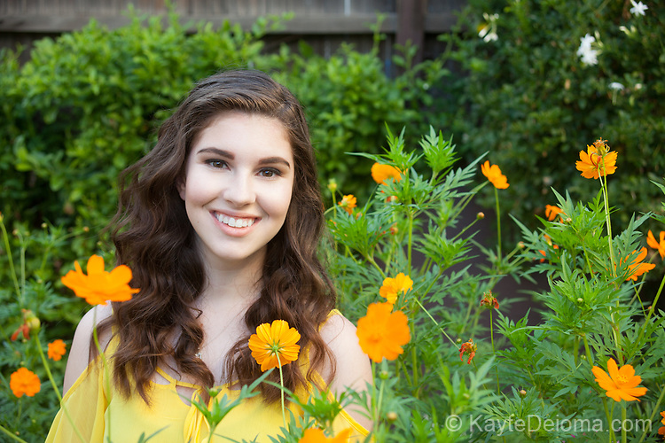 Portrait of a smiling teenage girl with dark brown hair in a garden with background of orange flowers