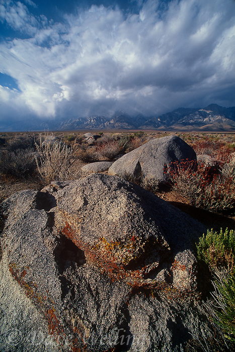 749200228 massive cloud formations from a gathering storm form over the eastern sierras mountain range and frame large granite boulders in kern county california