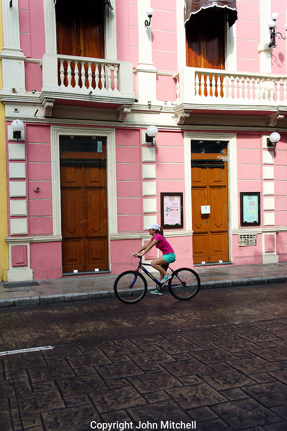 Young woman bicyclist riding by a pink Spanish colonial building on Calle Sesenta, Merida, Yucatan, Mexico.