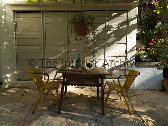 Two rusting chairs and an old table stand on the patio beneath a canopy of leafy vines