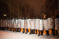 A deployment of riot police with shields during the night prepares for for the evacuations of the barricades around the government buildings. Kiev. Ukraine