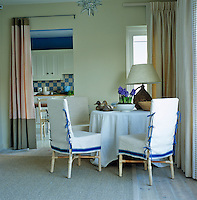 A curtain separates the kitchen from the dining area which is furnished with chairs covered in blue and white loose covers around a small round table