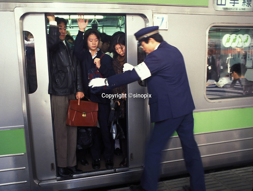 RAILWAY: TOKYO, JAPAN<br /> Commuters are squeezed onto a train during rush hour in central Tokyo.<br /> Photo by Richard Jones/sinopix<br /> &copy;sinopix