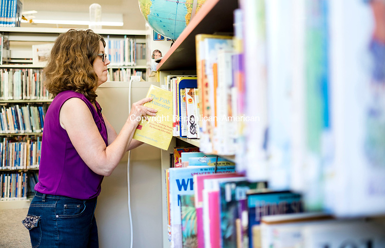 Woodbury, CT- 17 August 2017-081717CM02- Children's librarian, Denise Butwill organizes books inside the Woodbury Public Library on Thursday.  The children's section of the library will undergo renovations starting next week, which includes moving over 30,000 reading and audio visual materials.    Christopher Massa Republican-American