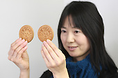 """Jan. 20, 2009; Obama, Fukui Prefecture, Japan - Chika Shimada, an employee at Wakasaya, holds up a japanese confectionery with President Obama's face and """"I Love Obama"""" slogan stamped on it."""