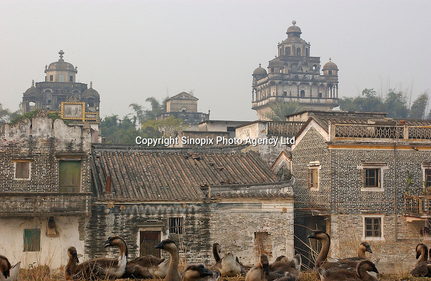 "A European ""tower"" in Jin Jiang Li dwarfs traditional houses in this town near Kaiping city in Guangdong Province, China. The European style ""towers"" were built by  .overseas Chinese returning with architectural ideas from America and Europe. The area is .one of the World Heritage Site.."