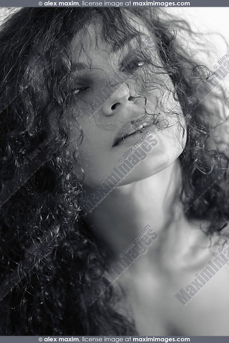 Natural close-up black and white beauty portrait of a young woman with long curly dark hair partially covering her beautiful face