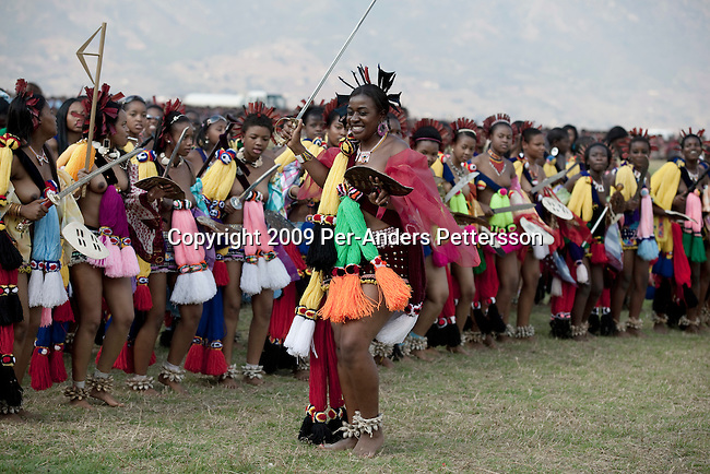 LUDZIDZINI, SWAZILAND - AUGUST 31: Members of the royal Swazi family dance with young girls dance at a traditional Reed dance ceremony at the stadium at the Royal Palace on August 31, 2009, in Ludzidzini, Swaziland. About 80.000 virgins from all over the country attended this yearly event, the biggest in Swazi culture. It was founded to celebrate the beauty of Swazi women and girls. King Mswati III, and absolute monarch, was born in 1968 and he has 14 wives and many children. The king danced with his men in front of the 80.000 girls. Many of the girls hope to get noticed by the king and to be chosen as a future wife, a ticket from poverty and into a life of privilege and luxury. The country is one of the poorest in the world and it is struggling with a high prevalence of HIV-Aids and severe poverty. (Photo by: Per-Anders Pettersson)..