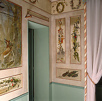A detail of a child's bedroom in the atelier of 19th century painter Charles Daubigny showing painted panels depicting foliage, toys and scenes of country life
