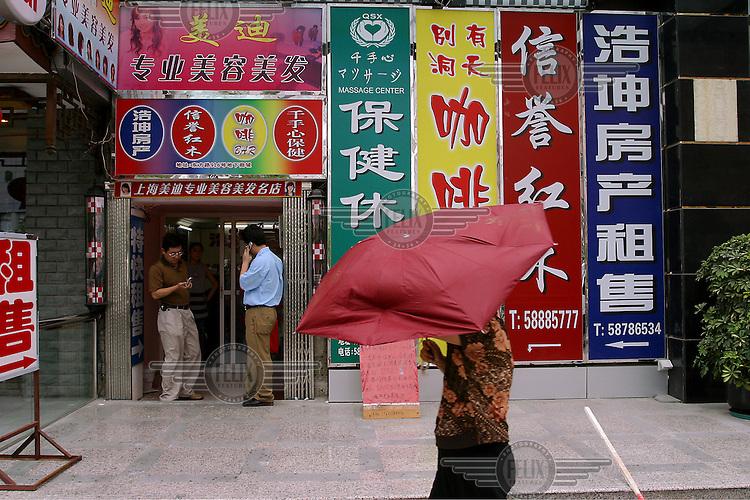 Men talking on mobile phones outside a 'massage centre'.