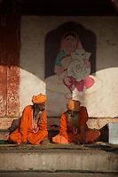 Priest reading the News paper Varanasi Ganges India
