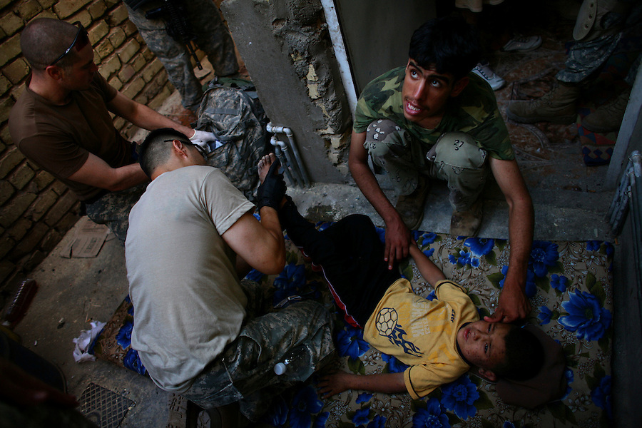 An Iraqi soldier touches an Iraqi boy's cheek in reassurance as American medics from US Army's Alpha Co. 5-20 Infantry 2nd Infantry Division change the dressings on the boy's injured foot after the child was delivered by his mother to the home where Alpha Co. had paused in its push forward while taking part in a large clearing operation to drive insurgents from the Khatoon District of the Diyala provincial capital, Baqubah, on Thurs. June 20, 2007.
