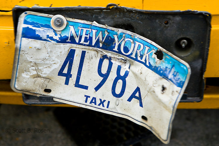 Close-up of a damaged New York City taxi license plate on an abandoned taxi in Red Hook, Brooklyn