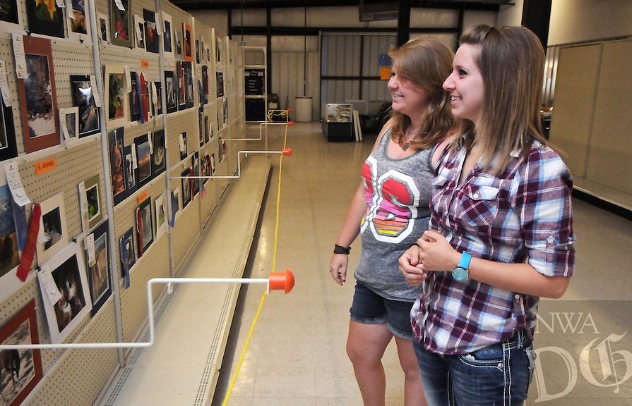 NWA Media/BEN GOFF  @NWABenGoff -- 08/12/14 Rebecca Tisdale, left, and sister Rachel Tisdale, of Gentry, look at the wining photography entries while perusing the fine arts and home arts displays at the Benton County Fair near Bentonville on Tuesday August 12, 2014.
