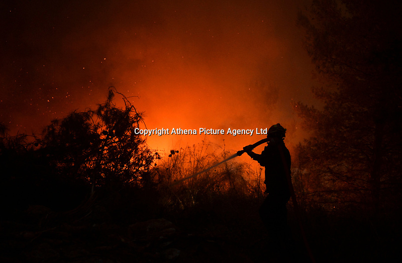 Pictured: A fireman battles with flames at near the village of Kapandriti.<br /> Re: A forest fire has been raging in the area of Kalamos, 20 miles north-east of Athens in Greece. There have been power cuts, country houses burned and children camps evacuated from the area.