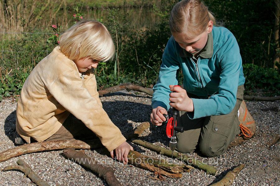 Kinder basteln Klangspiel aus Ästen, Mädchen bohrt mit Handbohrer ein Loch in Ast