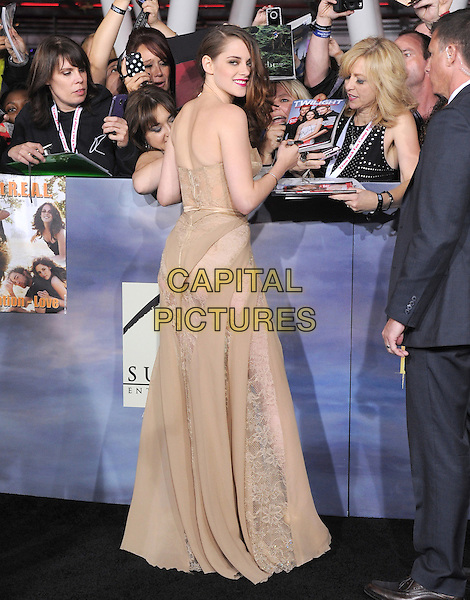 """Kristen Stewart (wearing Zuhair Murad Fall 2012).""""The Twilight Saga: Breaking Dawn - Part 2"""" Los Angeles Premiere held at Nokia Theatre L.A. Live, Los Angeles, California, USA..November 12th, 2012 .full length beige nude  corseted corset strapless gown lace chiffon panelling dress see through thru belt side swept hair back behind rear looking over shoulder fans crowd signing autographs .CAP/DVS.©DVS/Capital Pictures."""