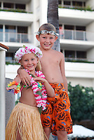 Brother and sister on vacation at hotel with hula outfit and swimming goggles