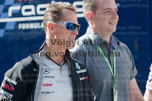 Mercedes Formula One driver Michael Schumacher (L) of Germany arrives to the paddock before the free testing session of