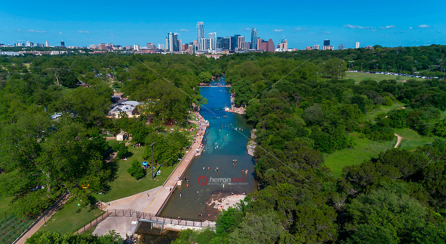 Gorgeous aerial drone view of Barton Springs Pool and the surrounding Zilker Park's lush green trees and grassy knoll with the ever booming Austin Skyline, pinnacle of Texas, and fastest growing city in America, towering above the natural landscaped park.