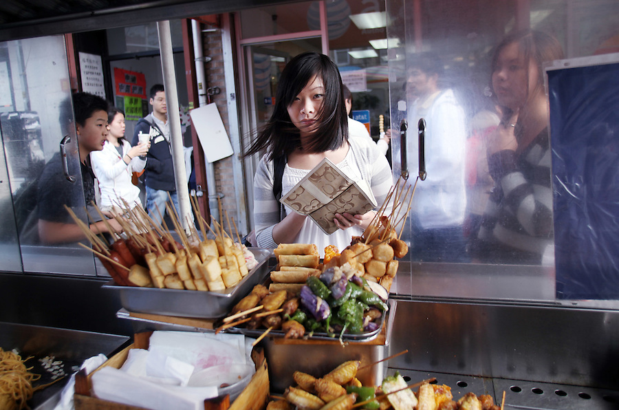 A young woman waits while her tofu kebab is deep fried at Linda's Mini Kitchen in Sunset Park, Brooklyn.